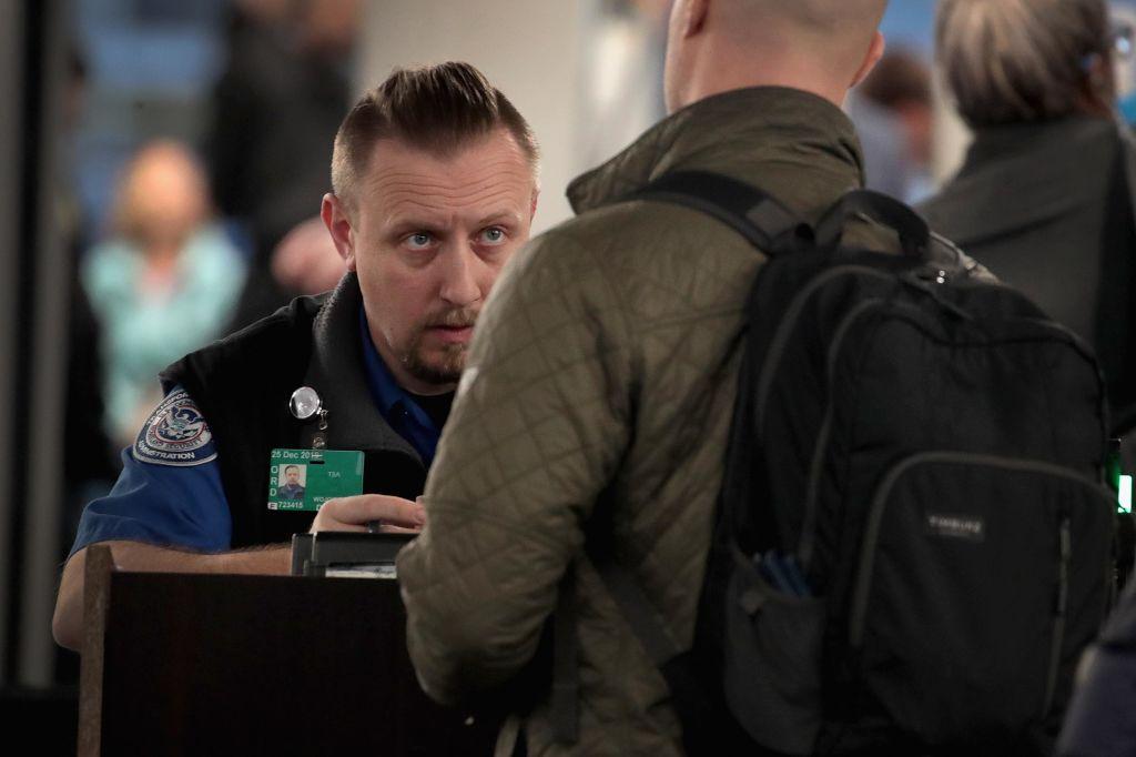 A TSA worker looks closely at a passenger.