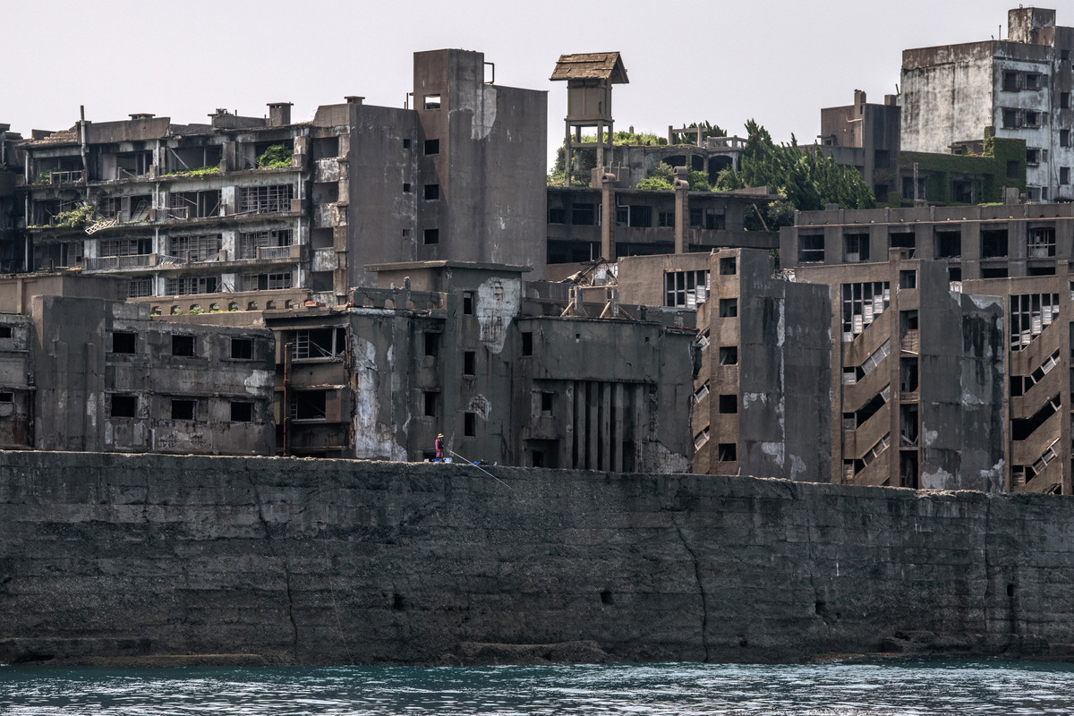 A man fishes from Hashima Island.