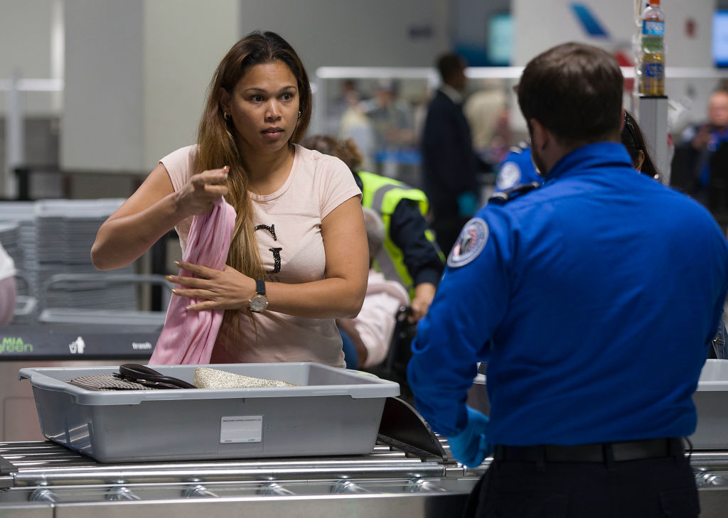 A woman looks seriously at a TSA worker.