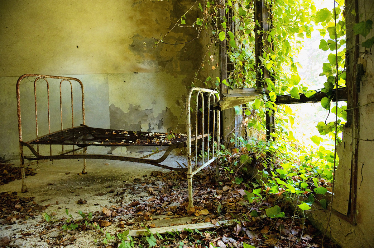 A bed frame remains in one of the dormitories in the psychiatric ward of the abandoned Hospital of Poveglia.
