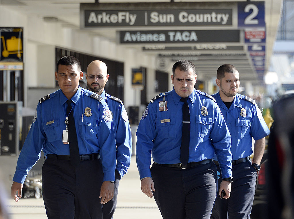 A group of TSA officers walk through an airport.
