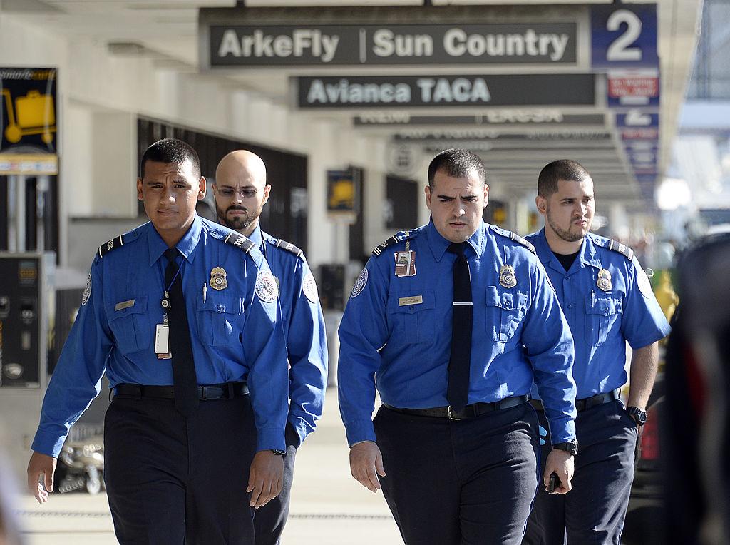 A group of TSA officers walk through an airport.