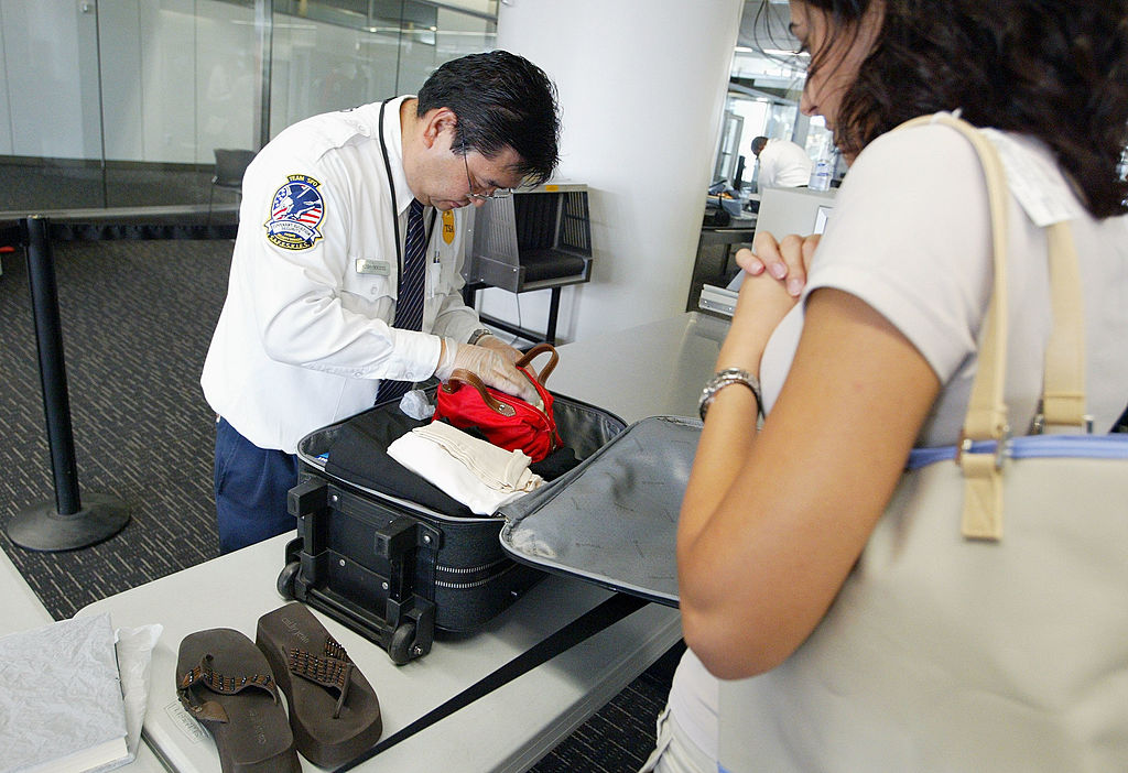 A TSA officer rummages through someone's suitcase.