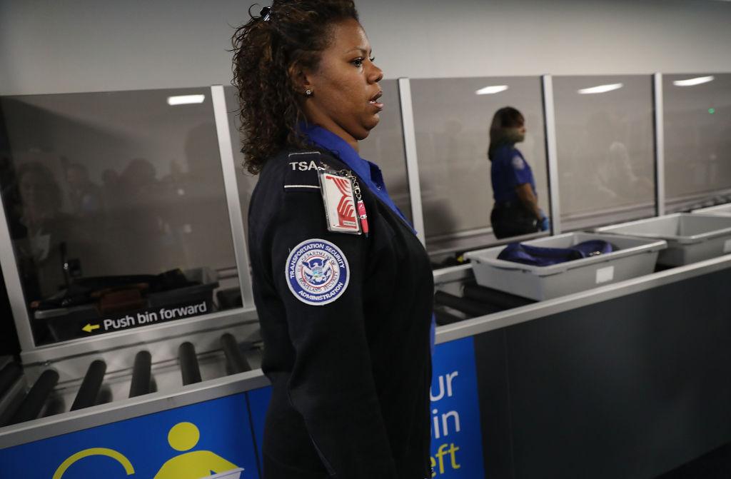 A TSA worker wears an annoyed facial expression.