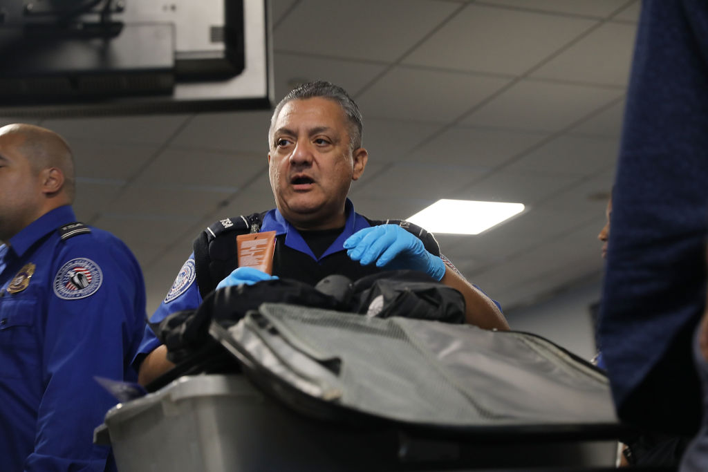 A TSA officer wears an open mouth while pausing from searching a bag.
