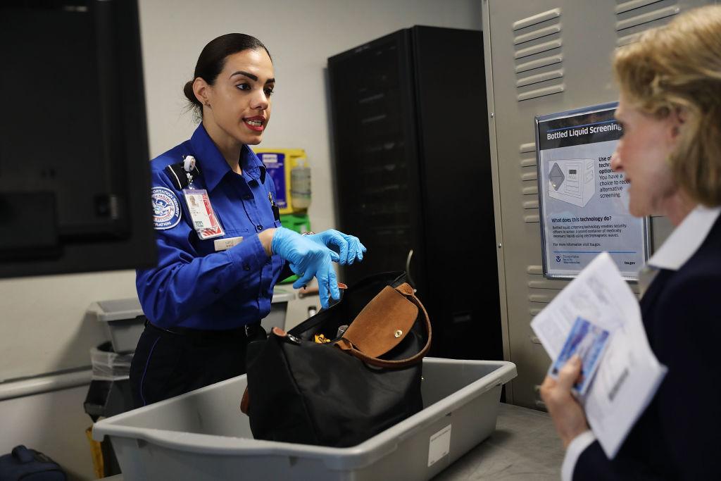 A woman TSA worker points to a passenger's bag.