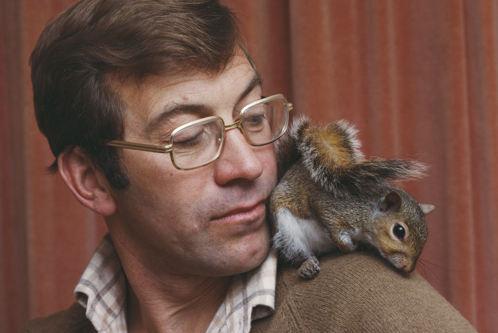 A man glances at a squirrel sitting on his shoulder.