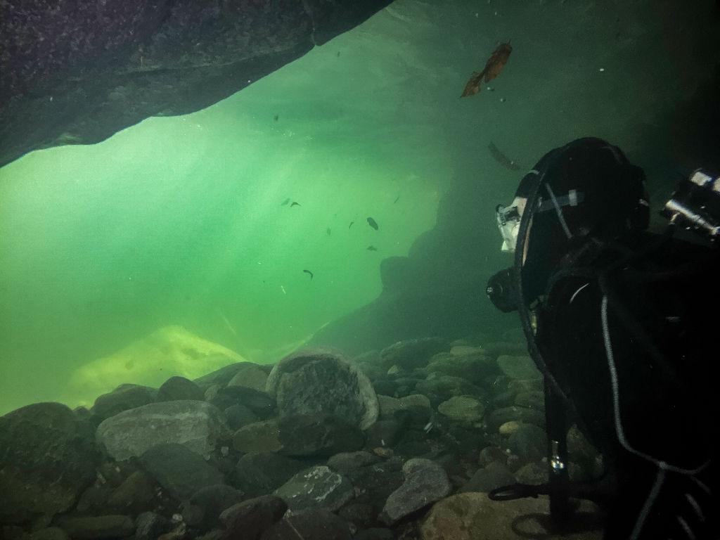 A scuba diver explores an underwater cave.
