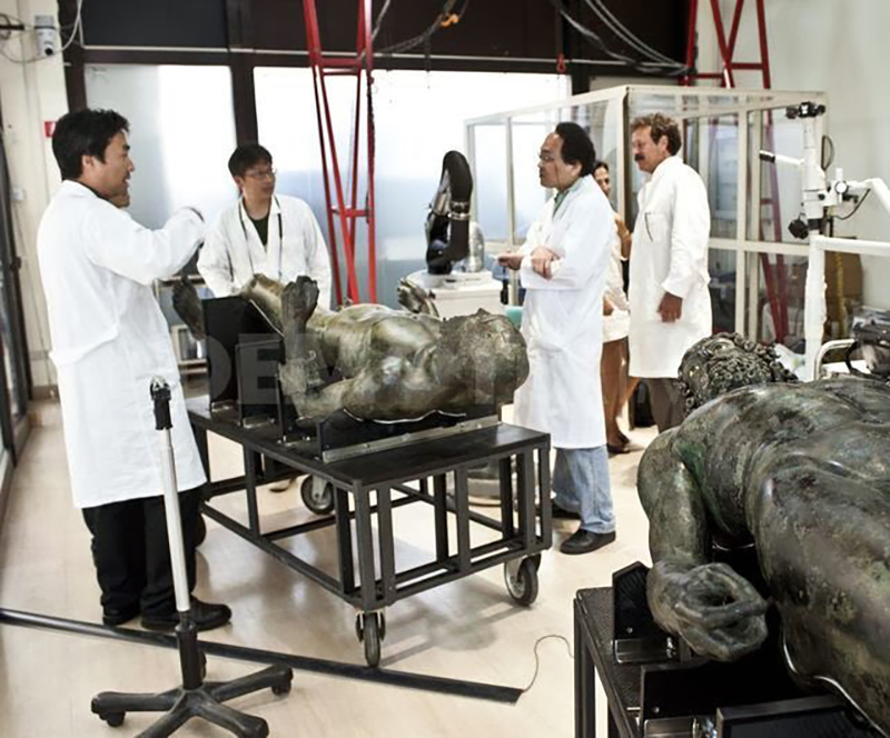 Experts gather around the statues in a lab.