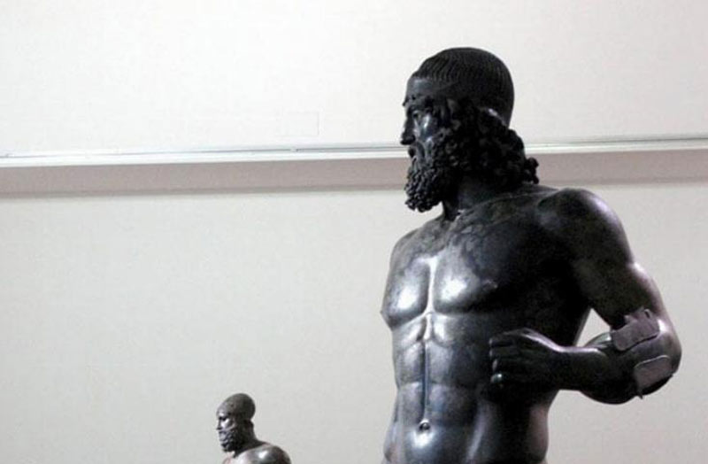 The two statues stand on display in a museum.