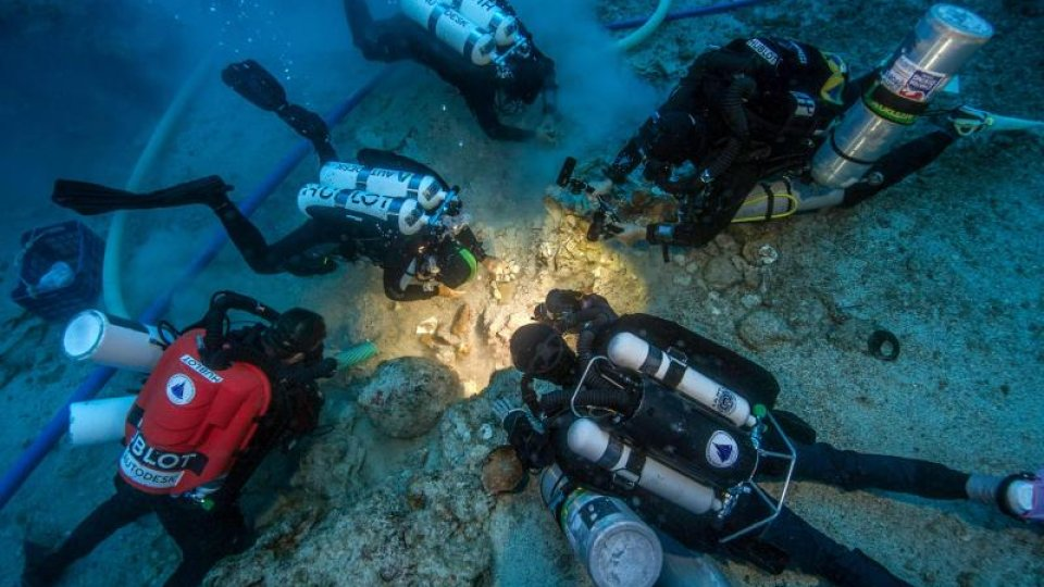 A team of scuba divers excavate something underwater.