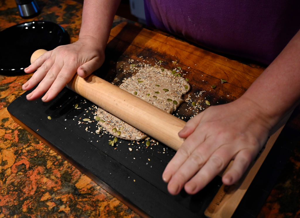 A chef rolls dough.