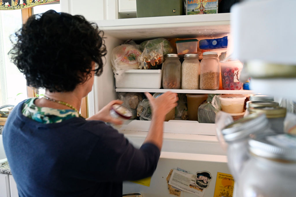A woman sorts items in a freezer.