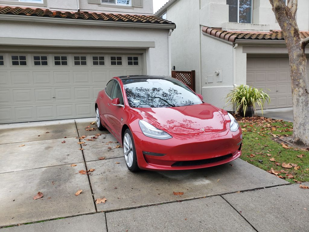 A red Tesla is parked in a driveway.
