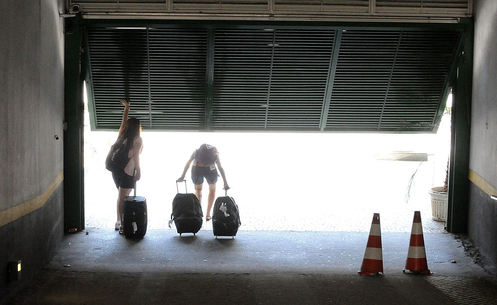 A couple with suitcase walk through a garage door.