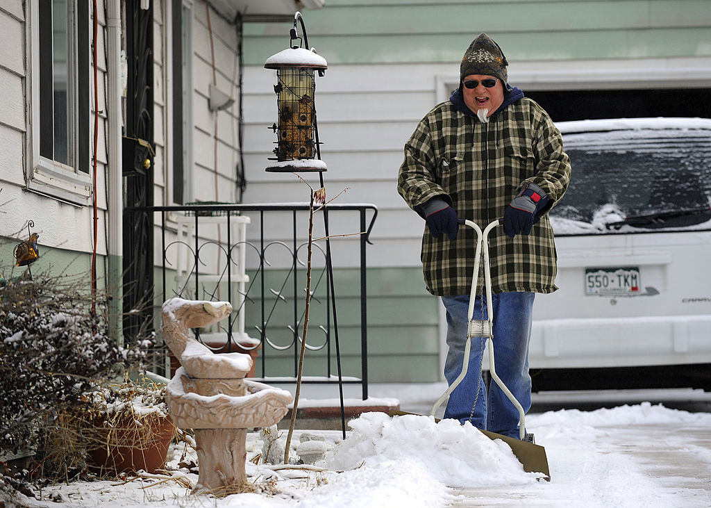 A man plows snow in his driveway.