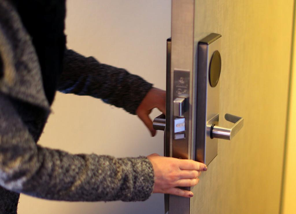 A woman checks the locks of a door.