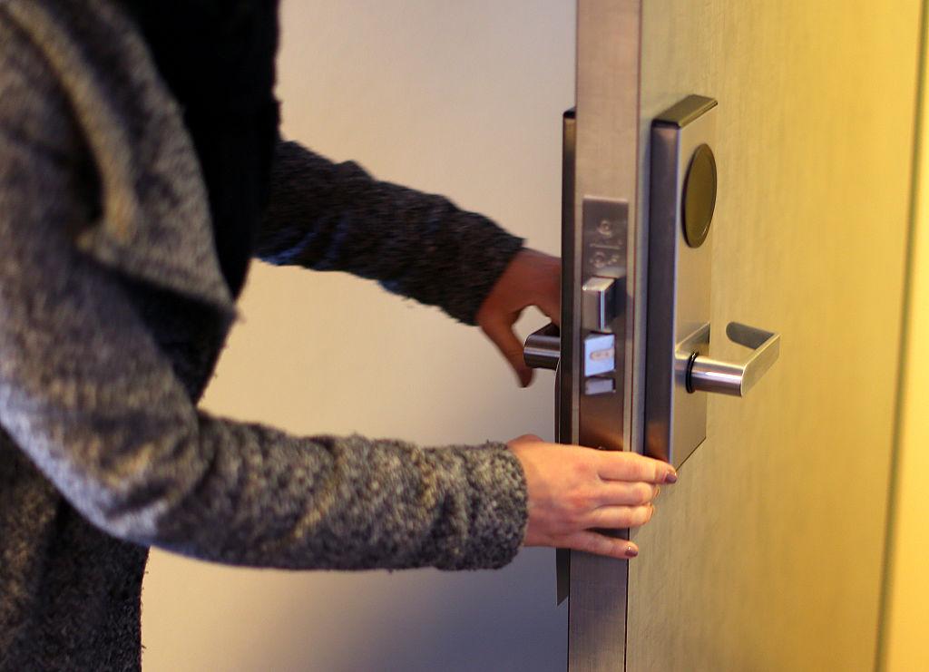 A woman checks the locks of a door.
