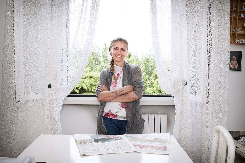 A woman smiles while standing in front of an open window.