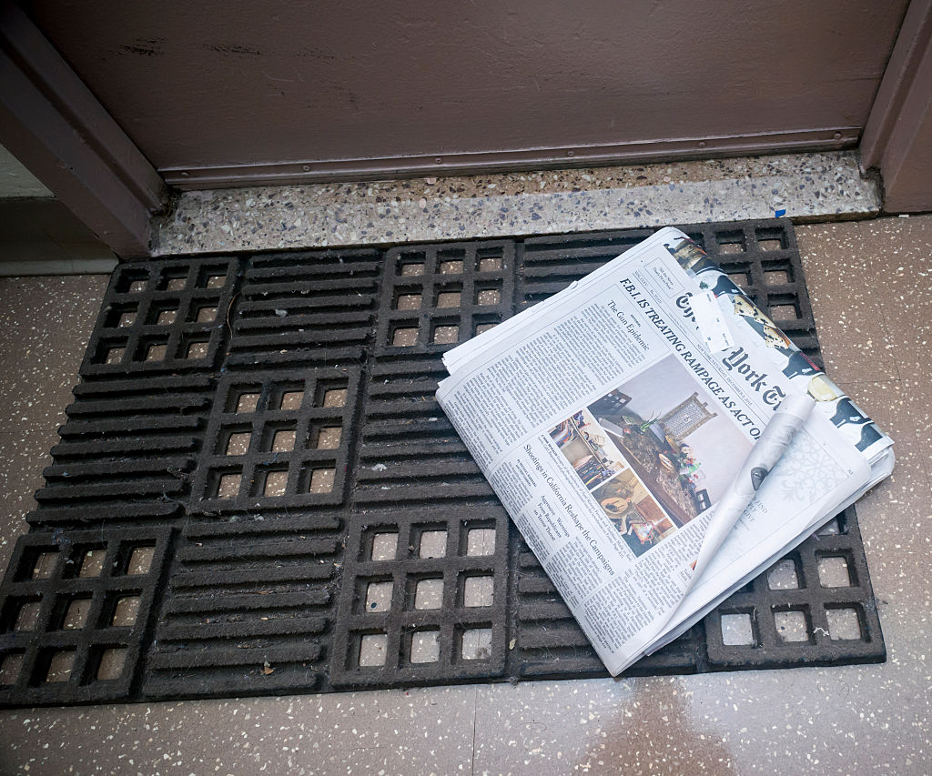 A newspaper sits on someone's welcome mat.