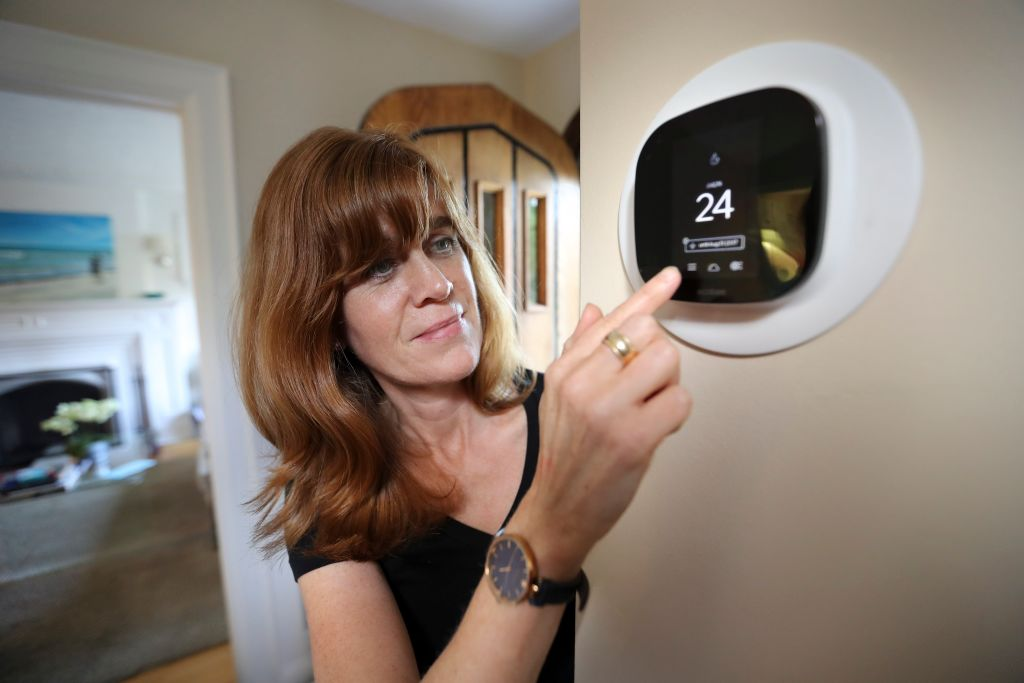 A woman adjusts her thermostat