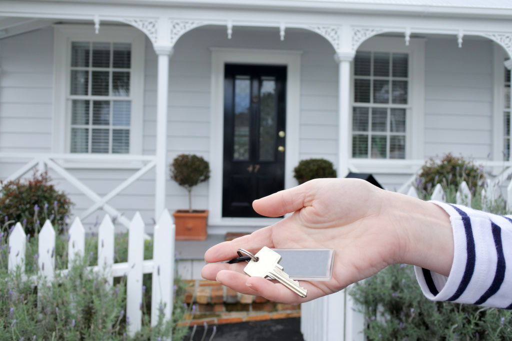 A woman holds out a key in front of a house.