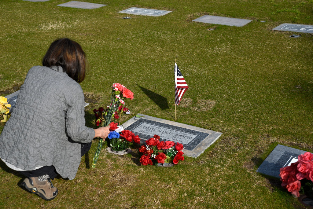 A woman places flowers on the grave of singer Frank Sinatra