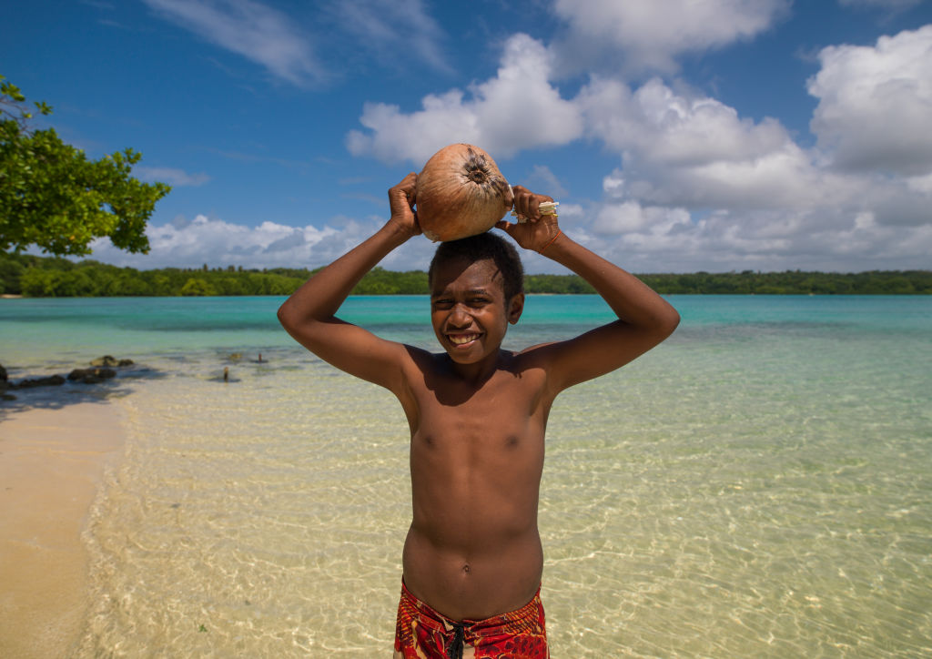 Young boy of the Ni-Vanuatu people with a coconut on his head,