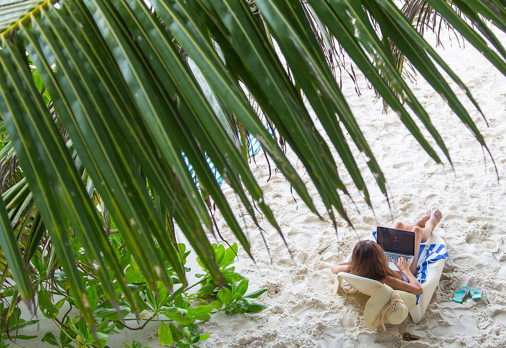 a woman on the beach working on her laptop