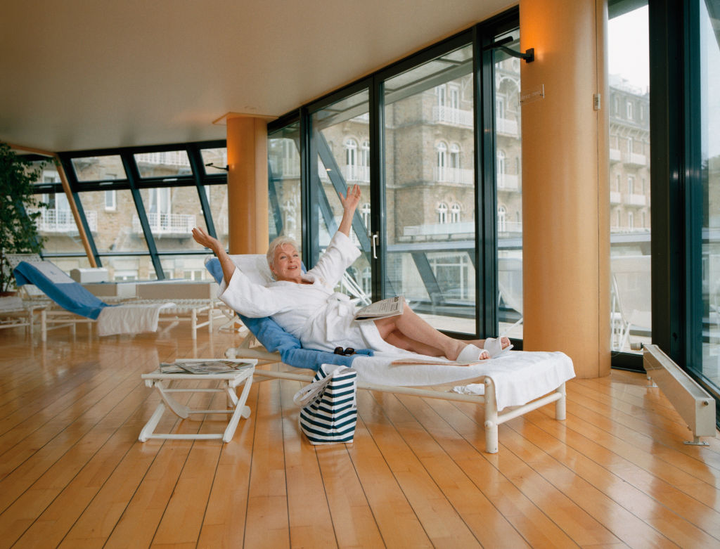a woman in a bathrobe relaxing on a lounge chair