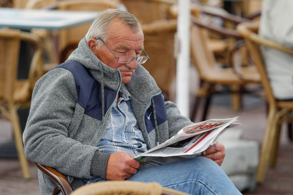 an old man reading a newspaper