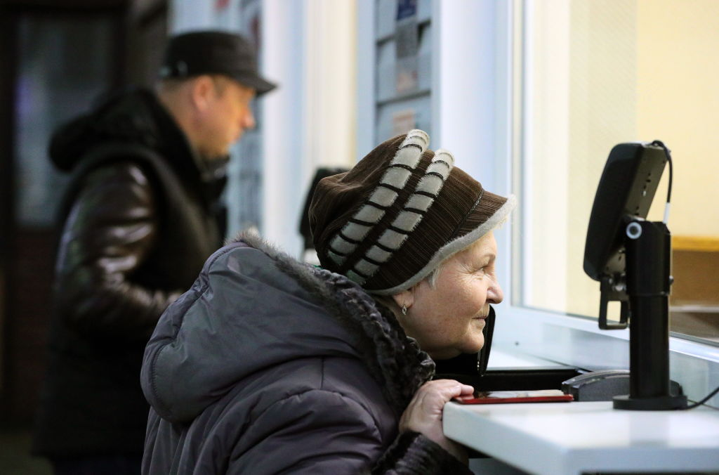 an elderly woman buying something at a ticket counter
