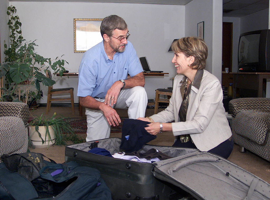 an older man and woman packing a suitcase in a home