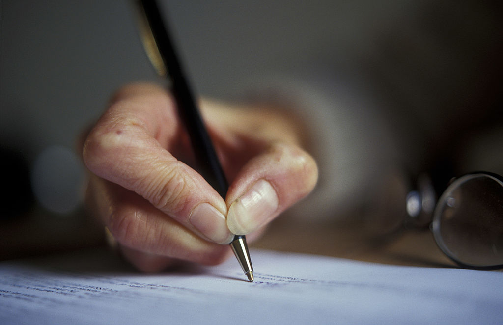 close-up of an elderly person writing with a pen on paper