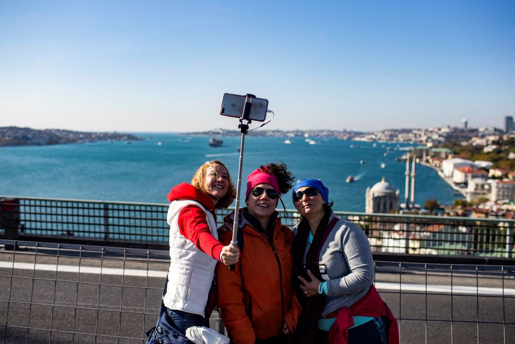 three women taking a selfie on a bridge