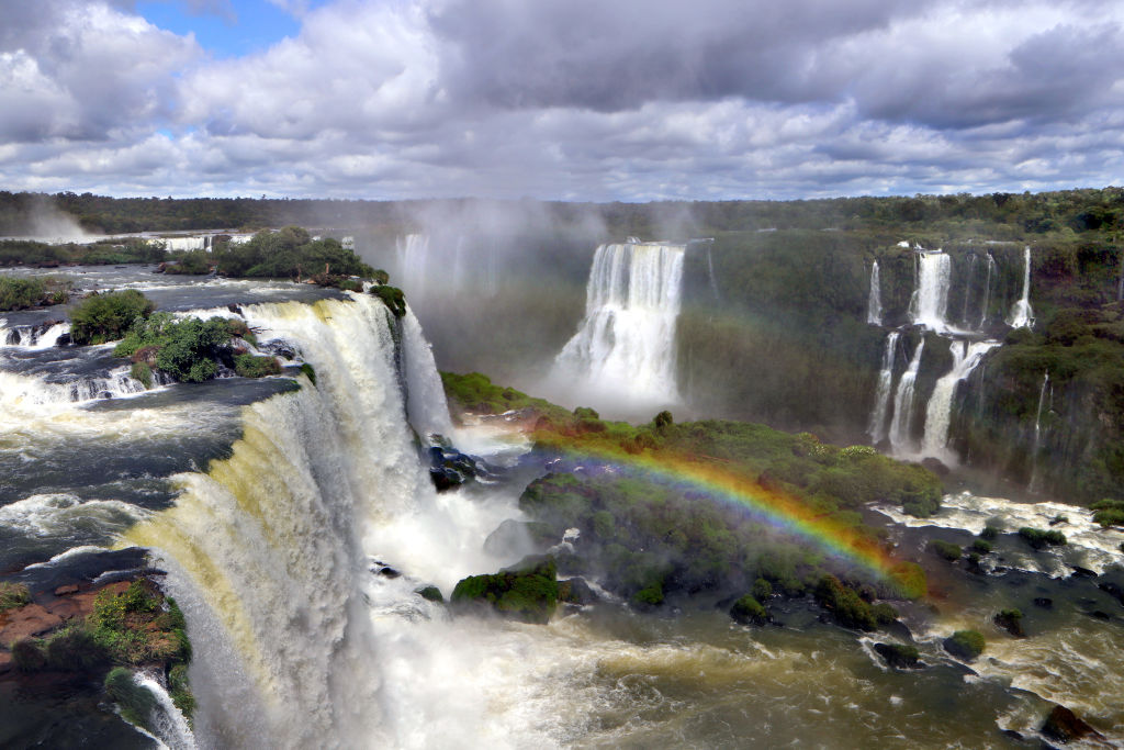 a rainbow in the middle of Iguazu Falls waterfalls in brazil