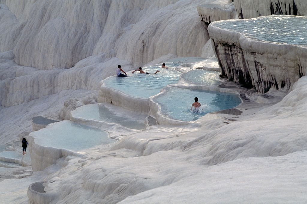 people swimming in the Pamukkale Thermal Pools along a white mountain