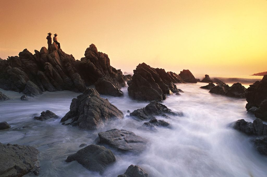two men standing on top of rocks near the ocean in Puerto Escondido