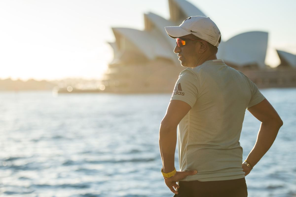 a man standing near the harbor by the sydney opera house in australia