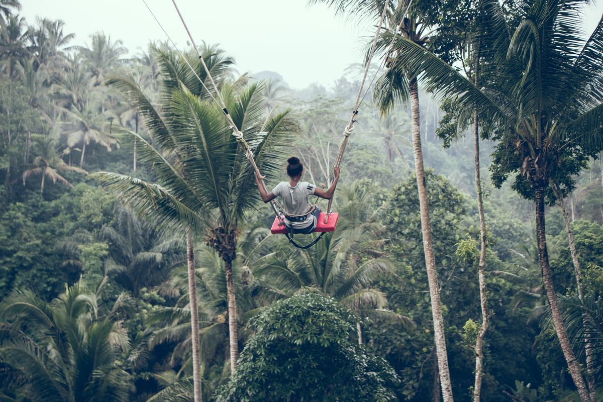 a girl swinging atop palm trees in bali