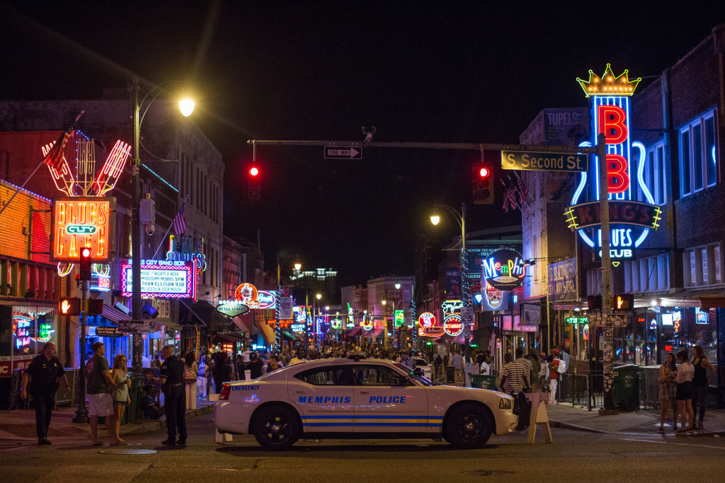 a shot of beale street lit up at night with a police car and crowd of people