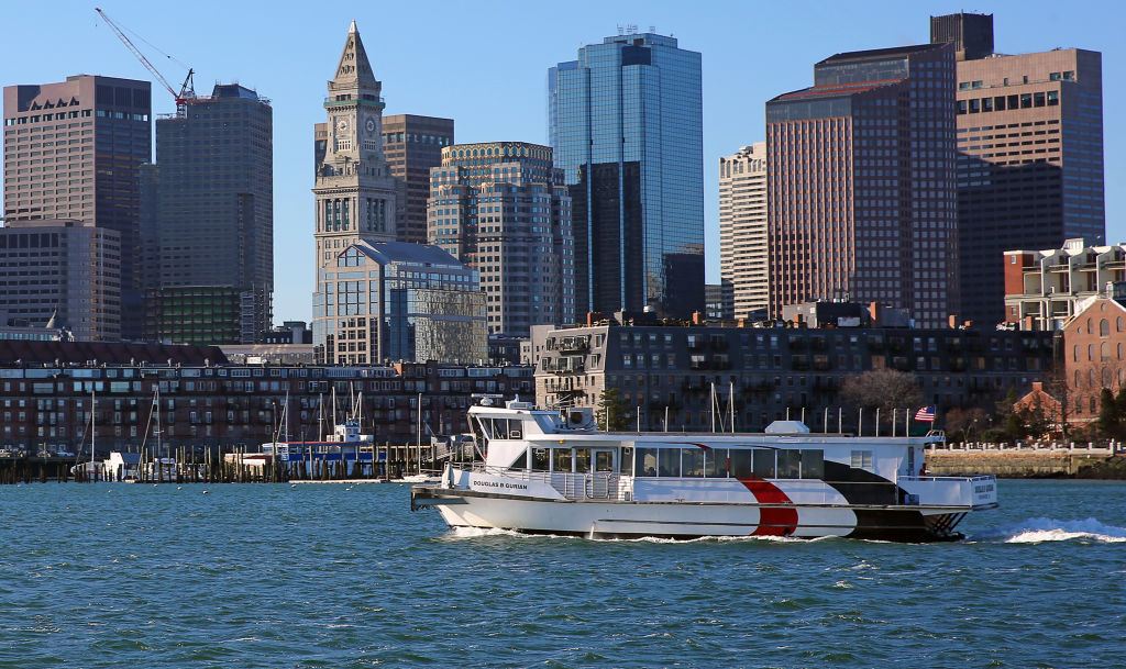 a commuter boat in the pier in front of the boston city skyline