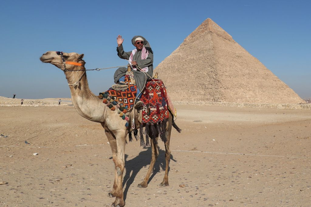 an egyptian man riding a camel in front of a pyramid in egypt