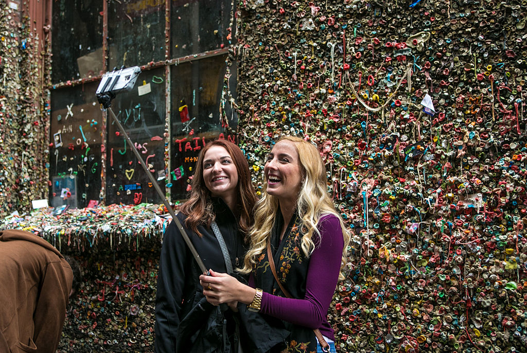 two girls taking a selfie in front of a gum wall