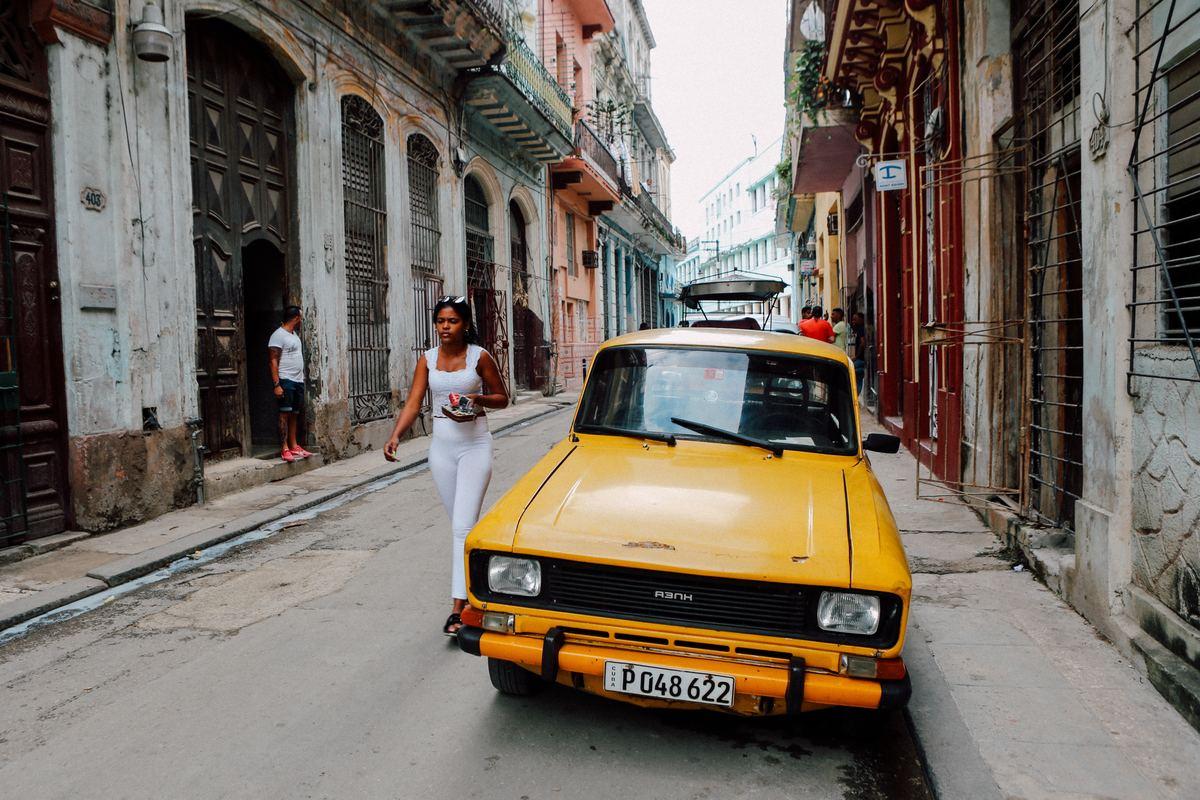 a woman walking by a taxi in havana, cuba