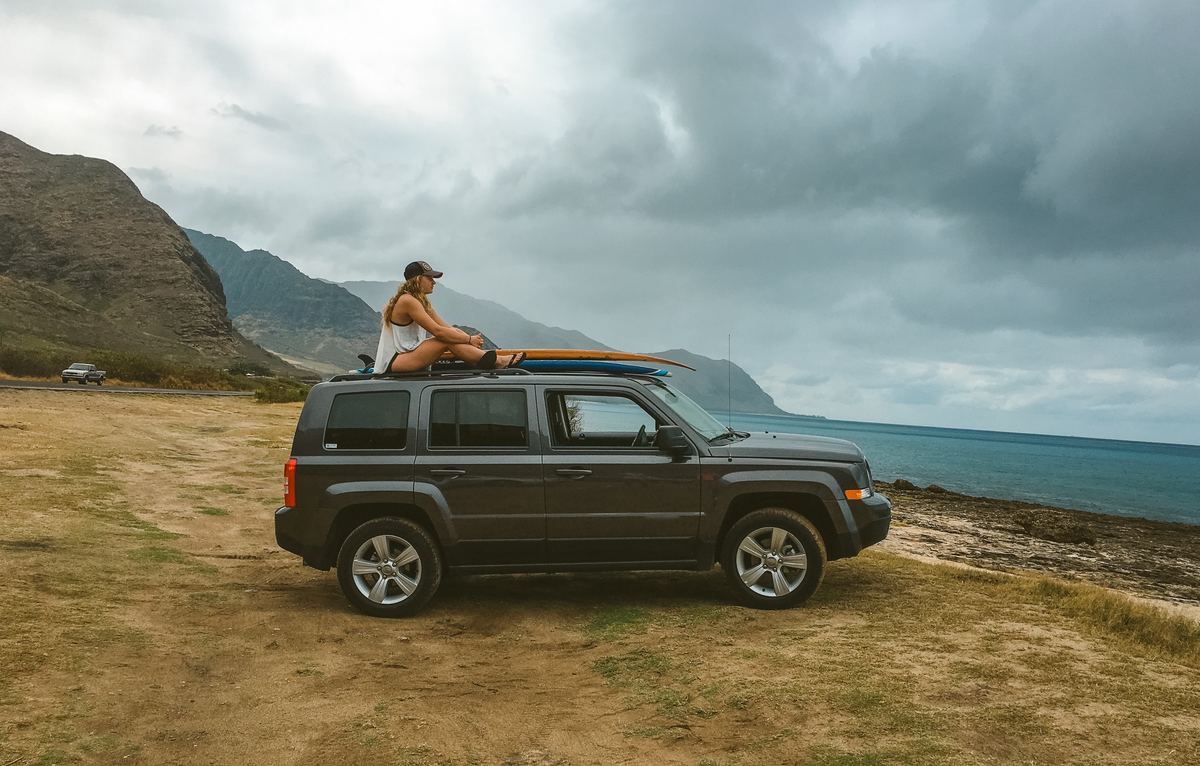 a girl sitting on top of a car on the beach in hawaii