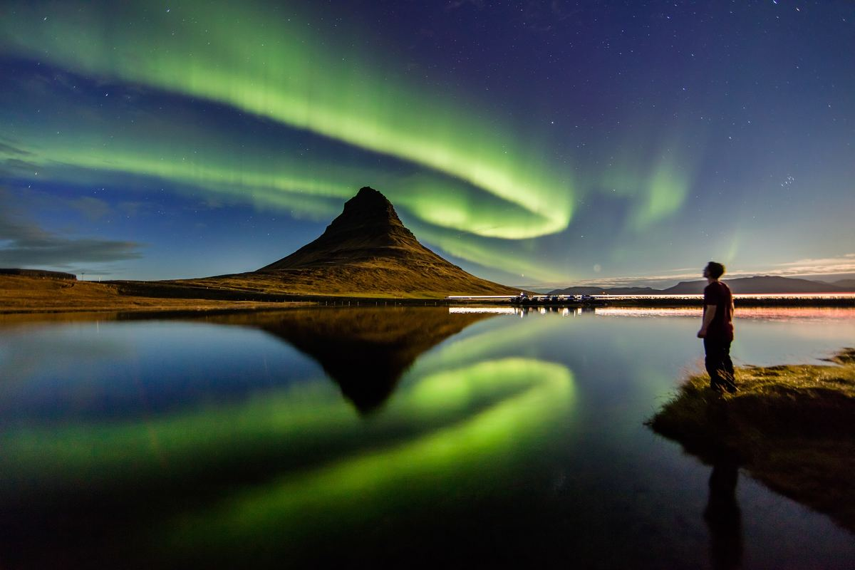 a man looking up at the northern lights in iceland