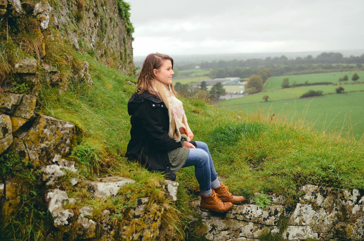 a girl sitting on a grassy hill in ireland