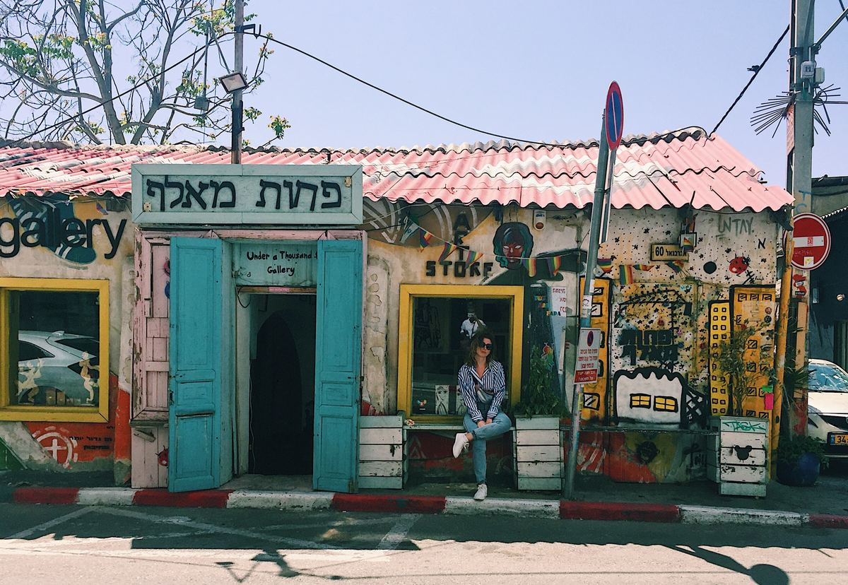 a woman sitting outside a store in israel