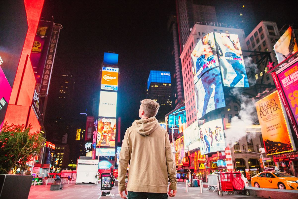 a boy standing in times square in new york city